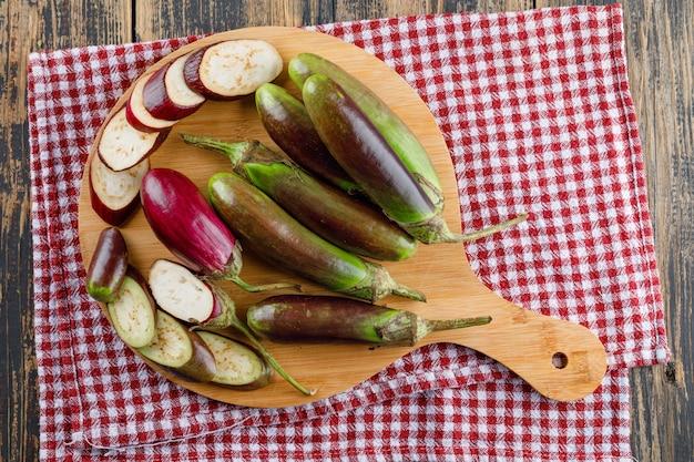 Баклажаны и ломтики на разделочную доску на деревянных и кухонное полотенце. плоская планировка