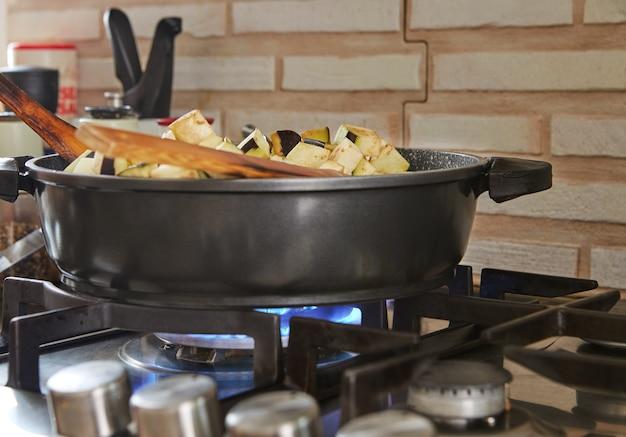 Баклажаны жарят на сковороде на газовой плите на кухне по рецепту из интернета.