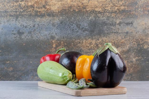 Баклажаны, болгарский перец и цукини на деревянной тарелке. фото высокого качества
