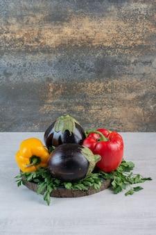 Melanzane, peperoni e prezzemolo sul pezzo di legno. foto di alta qualità