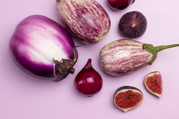ナス、紫玉ねぎ、イチジクをテーブルに。ピンクの背景。上面図。
