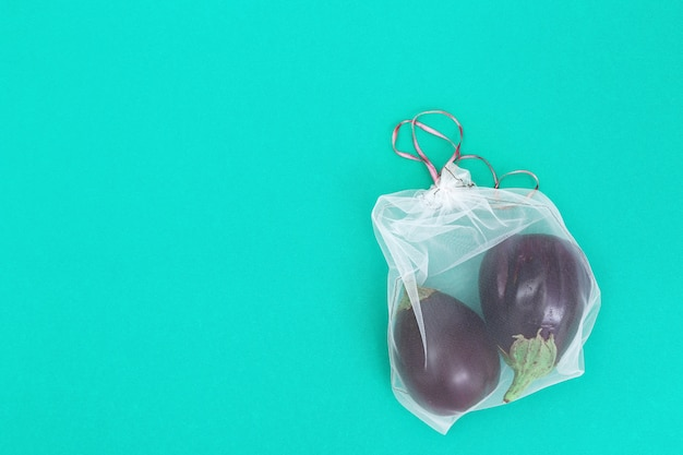 Eggplants in reusable eco bags. fresh vegetables in bags from transparent textile for food storage. plastic free concept. flat lay. top view.
