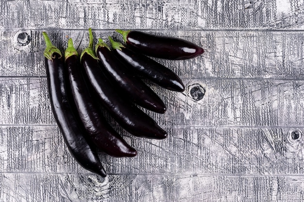 Eggplants sorted by size top view on a gray wooden  space for text