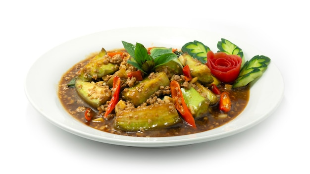 Жареные баклажаны с фаршем из свинины, перцем чили и базиликом в тайфудском стиле украшают резные овощи, вид сбоку