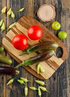 Eggplants with tomatoes, peppers, green plums, wood on wooden and cutting board, flat lay.