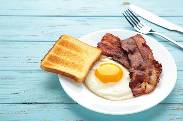 파랑에 아침 식사를 위해 계란과 베이컨.