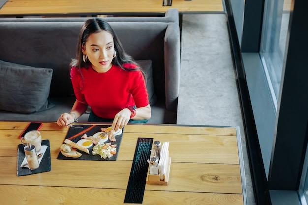 卵とコーヒー。朝食に卵を食べ、コーヒーを飲む黒髪のスタイリッシュな女性