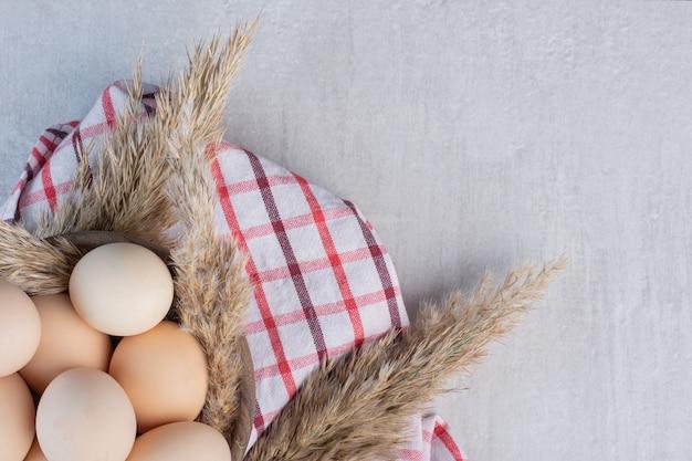 Яйца и ковыль стебли рядом с миской на полотенце на мраморном столе.