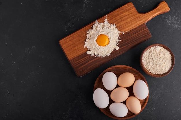 Яйца и мука в деревянных тарелках для выпечки.