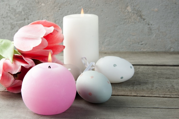 Eggs and aroma candles on old wooden background