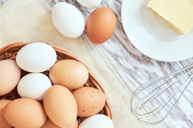 Eggs in basket, butter and whisk, top view, stylized