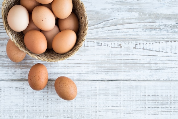 Eggs in a basket on a white wooden floor.