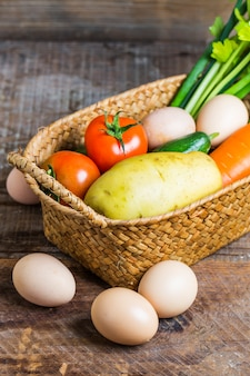 Eggs next to a basket with vegetables