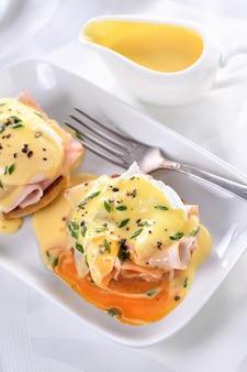 에그 베네딕트. 튀긴 영국식 번, 햄, 수란, 맛있는 hollandaise 버터 소스