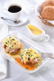 Eggs benedict - fried english bun, ham, poached eggs and delicious hollandaise   butter sauce