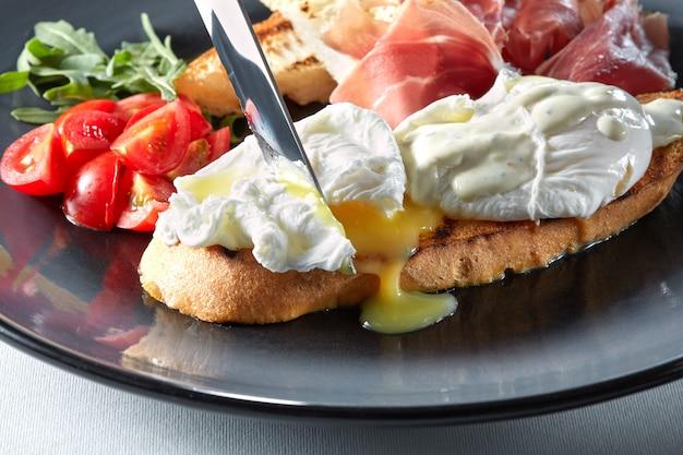 햄, 토마토, 소스를 곁들인 구운 빵에 달걀 베네딕트