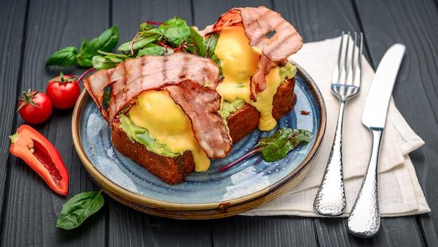エッグベネディクト-トースト、ベーコン、ポーチドエッグ、そしておいしいバターオランデーズソース。レストラン