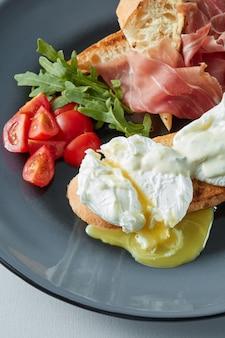 햄과 토마토를 곁들인 에그 베네딕트와 치즈 토스트