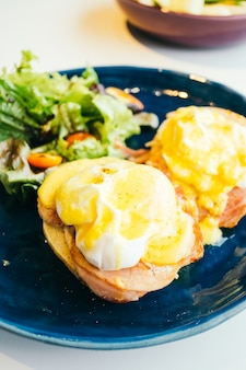 Eggs benedict with ham and sauce on top