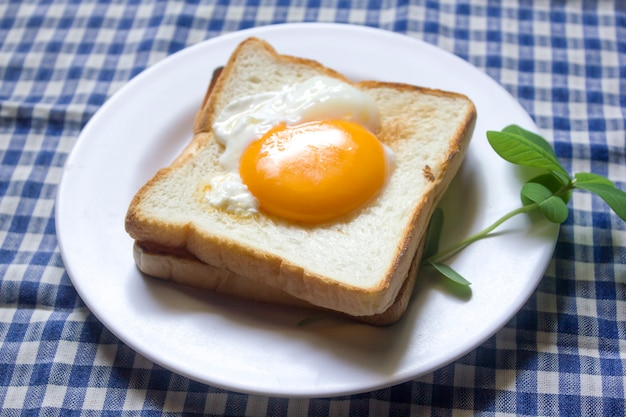 The eggs on the bread are in a white plate.
