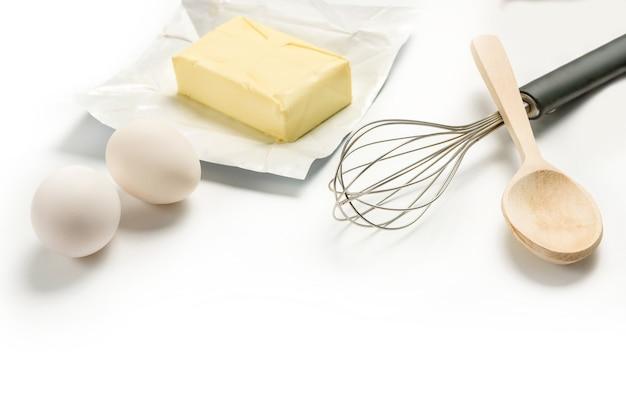 Яйца, масло, венчик и деревянной ложкой на белой тарелке с копией пространства. домашняя выпечка.