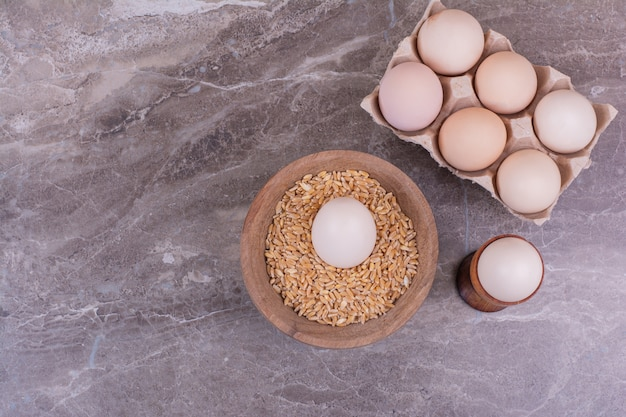 Eggs in a cardboard tray and on wheat grains.