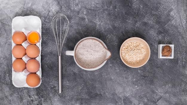 Eggs carton; whisks; walnut; flour and oat bran on concrete backdrop