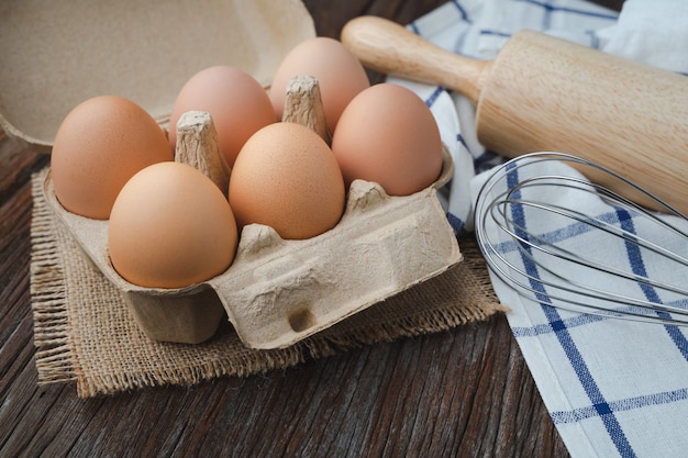 Eggs in carton with whisk and rolling pin on wooden table for cook and bakery concept