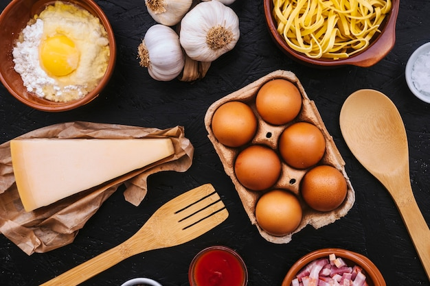 Eggs and cheese amidst pasta ingredients and utensils