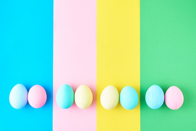 Eggs on colored striped background, top view, minimalism concept