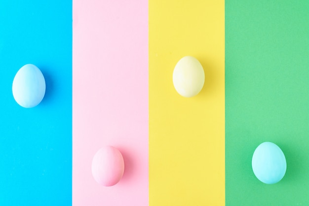 Eggs on colored striped, minimalism concept