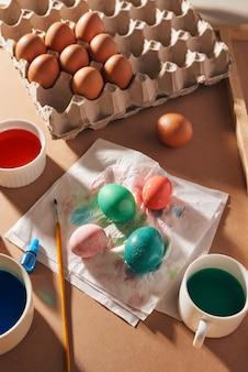 卵、カラフルな絵の具、ブラシ、木製の背景に鉛筆、卵の着色、イースターの準備、春の季節の休日