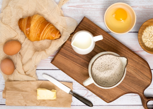 Eggs; croissant; butter; milk; flour and oats bran on wooden desk