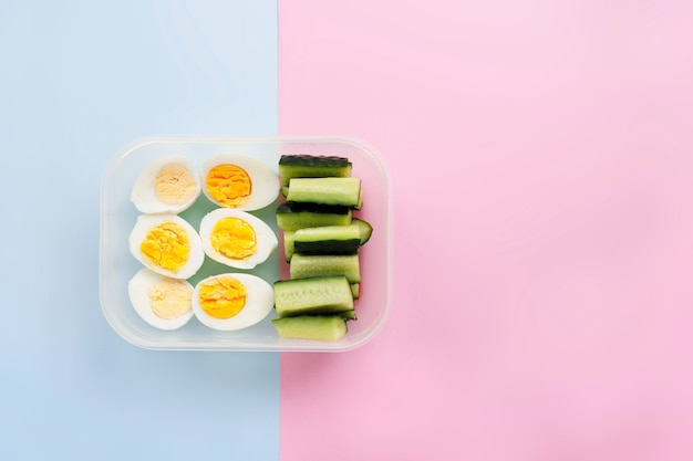 Eggs and cucumber in a container. healthy eating concept. top view. flat lay
