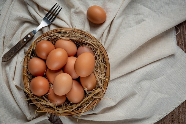 Eggs in cups on burlap with dry grass.