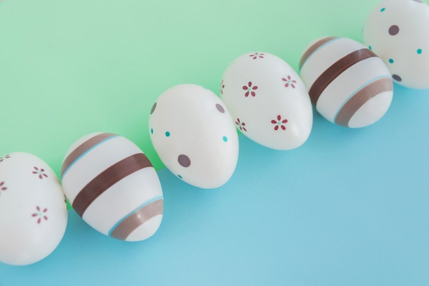 Eggs decorated with stripes and flowers on green and blue background, easter concept.