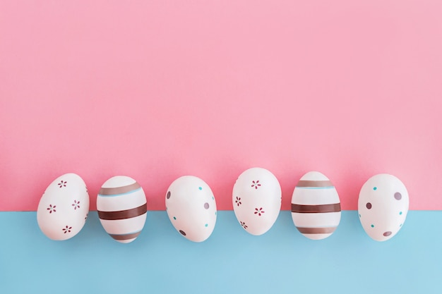 Eggs decorated with stripes and flowers on pink and blue background, easter concept.