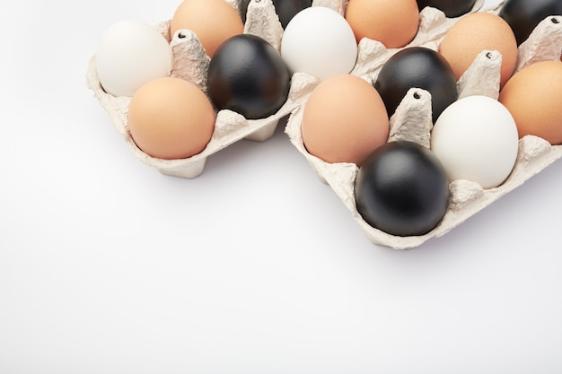 Eggs of different colors in cardboard boxes.