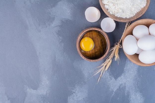 Uova, gusci d'uovo e tuorlo d'uovo in una tazza di legno