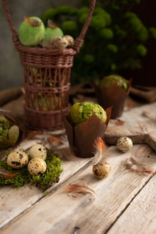 Eggs, feathers and muffins with pistachio on light wooden table