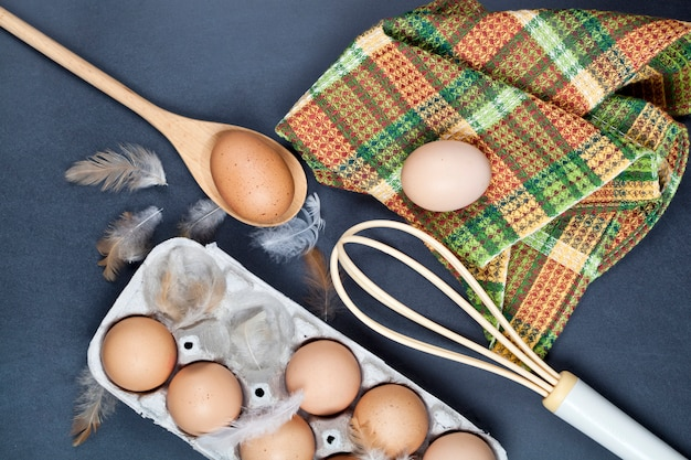 Eggs and feathes on backboard background.