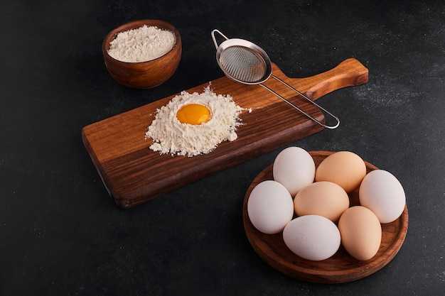 Eggs and flour as cooking ingredients on wooden board.