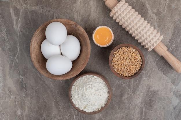 大理石の表面に卵、小麦粉、大麦、麺棒。高品質の写真
