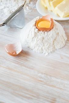 卵、小麦粉、バター、パスタ、または木製のテーブルのベーキング成分。セレクティブフォーカス