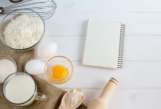 Eggs, flour, milk, with whisk on white wooden table from above.