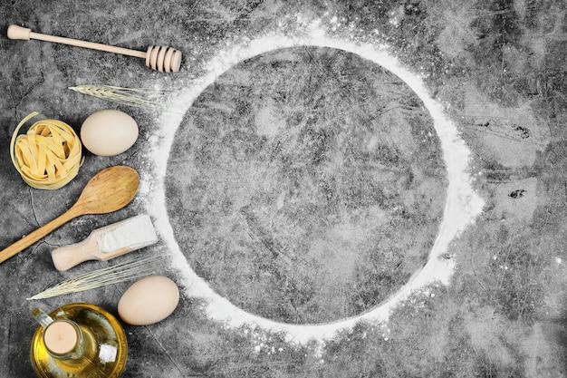 Uova, farina, olio, pasta cruda e cucchiai di legno su marmo.