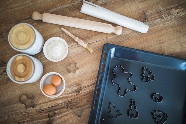 Uova, farina, mattarello e forme per biscotti sulla leccarda