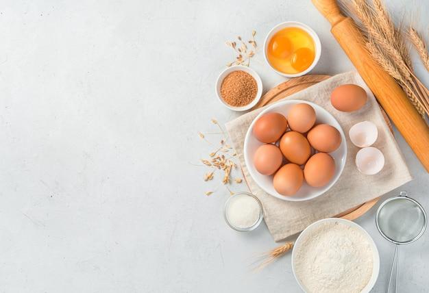 ベーキングのための灰色の背景の材料に卵粉砂糖麺棒と小麦