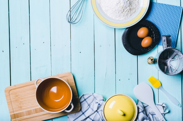 Eggs and flour with a rolling pin on wooden background
