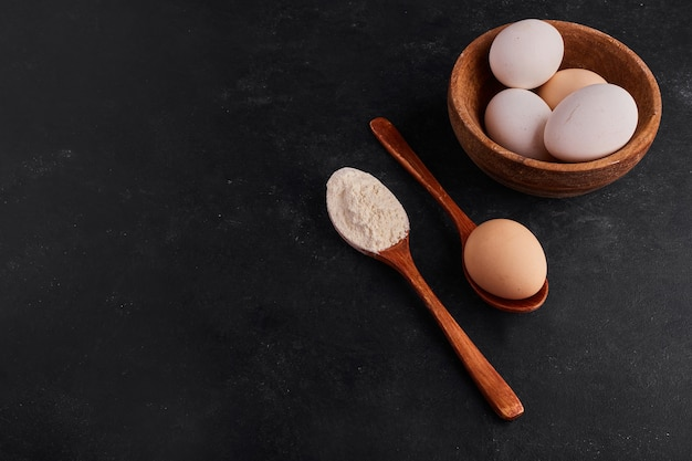 Eggs and flour in wooden dishes.